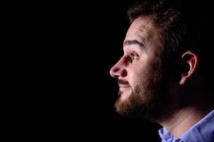 Smiling face in the dark. Man with beard looks smiling into the darkness Royalty Free Stock Image
