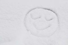 A smiling face drawing on snow. Cute and warm drawing in cold winter stock photography
