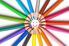 Smiling face drawn in a circle of colorful wooden pencils isolated on white, school art and education concept. Smiling face drawn in a circle of colorful wooden stock photo