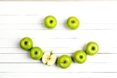 Smiling face of green apples on white wooden table. Apple emotic. On. Top view Stock Images