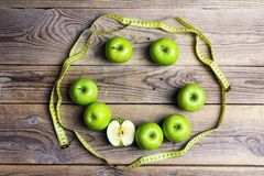 Smiling face of green apples and yellow centimeter tape on old w. Ooden background. Apple dieting emoticon. Top view. Concept  diet and healthy eating Royalty Free Stock Images