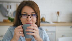 Smiling face of happy young woman in glases drinking coffee from grey blue mug