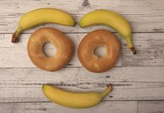 Smiling face made from bagels and fruit. On a wooden background royalty free stock photos