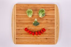 Smiling face made of Brussel sprouts broccoli floret cherry tomatoes. Happy face smiley face made of vegetables Brussel sprout eyes broccoli florets cherry stock photos