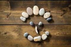 Smiling face made from pebbles on a wooden floor. Face made from beach pebbles with a happy smiling expression on a wooden rustic table. Concepts for health Stock Image
