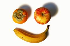 Smiling face made of persimmon apple and banana. One smiling face background made of persimmon, Gala apple and a yellow banana Stock Photos