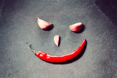 Smiling face made of red chili pepper and cloves of garlic Stock Images