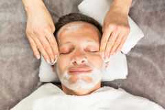 Smiling face of man with cream mask and towels Stock Photo