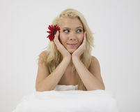 Smiling face of model with red gerbera in hair Royalty Free Stock Photography