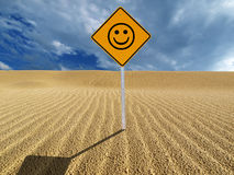 Smiling face sign in desert. A road sign with a happy, smiling face in the middle of a desert sand dune Stock Photo