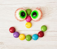Smiling face of smarties and chewing gums in the form of eyes. Funny confectionery Stock Photos