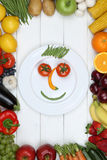 Smiling face from vegetables and fruits on plate Royalty Free Stock Photo