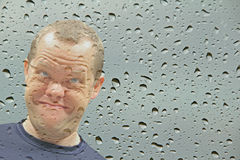 Smiling face at wet window Stock Photos