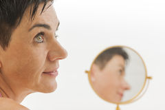 Smiling face of woman with mirror Stock Photo