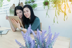 Smiling face women using tablet in workplace at home, Workplaces. House with trees and flowers on garden. concept of lifestyle of Asian women Royalty Free Stock Photo