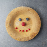 Smiling face on a wooden plate with raspberries and blueberries. On gray background Royalty Free Stock Photography
