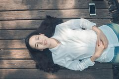 Smiling face Young asian woman in white shirt, blue jean sleepin. G on wood floor and blank screen on smart phone, tablet, cellphone. concept of asian woman Royalty Free Stock Images