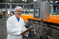 Smiling factory engineer maintaining record on clipboard in factory stock images