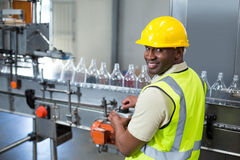 Smiling factory worker operating machine in factory Royalty Free Stock Photo