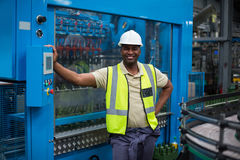 Smiling factory worker standing near machine control cabinet. In factory Royalty Free Stock Images