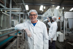 Smiling factory worker standing next to production line. At drinks production plant Royalty Free Stock Photos