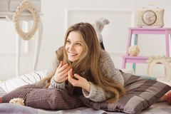 Smiling fair-haired woman lying on bed with pillows stock photos