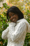 Smiling on a fall day. African american woman smiles in a white sweater on a beautiful fall day royalty free stock photo