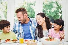 Smiling family with arm around while sitting at dining table Royalty Free Stock Photography