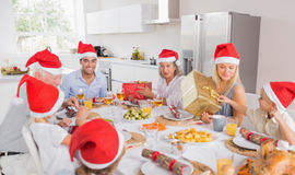 Smiling family around the dinner table. Smiling family at the dinner table at christmas exchanging gifts wearing santa hats Royalty Free Stock Images