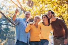 Family on an autumns day in park make selfie photo. Smiling family on an autumns day in park make selfie photo stock photos