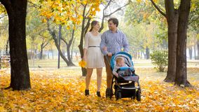Happy smiling family with baby boy boy in pram walking on yellow leaves at autumn park. Smiling family with baby boy boy in pram walking on yellow leaves at Royalty Free Stock Photo