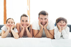 Smiling family in bed. Smiling family lying together on bed Royalty Free Stock Image