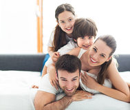 Smiling family in bed. Smiling family lying together on bed Royalty Free Stock Photos
