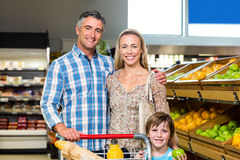 Smiling family behind their trolley Royalty Free Stock Photos