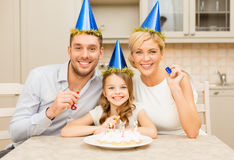 Smiling family in blue hats blowing favor horns Royalty Free Stock Photo