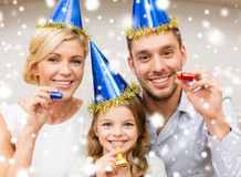 Smiling family in blue hats blowing favor horns. Celebration, family, holidays and birthday concept - three smiling women wearing blue hats and blowing favor royalty free stock image