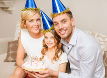 Smiling family in blue hats with cake Royalty Free Stock Photography