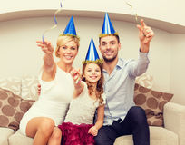 Smiling family in blue hats with cake Royalty Free Stock Photos