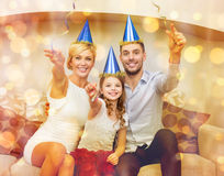 Smiling family in blue hats with cake Royalty Free Stock Image