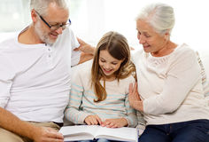 Smiling family with book at home royalty free stock photo