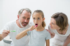 Smiling family brushing their teeth with toothbrush Stock Photography