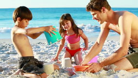 Smiling family building sand castles stock video
