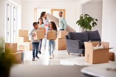 Free Smiling Family Carrying Boxes Into New Home On Moving Day Royalty Free Stock Photos - 157263078