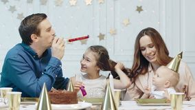 Smiling family celebrating new year in luxury house together. Cheerful man tootling birthday pipes in christmas decorated apartment. Happy couple with two kids stock footage