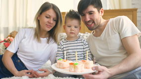 Smiling family celebrating their son birthday together before blowing candles on cake stock footage