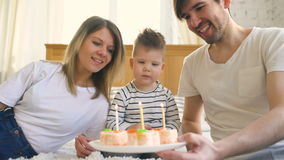 Smiling family celebrating their son birthday together before blowing candles on cake stock video