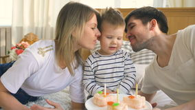 Smiling family celebrating their son birthday together and blowing candles on cake stock video footage