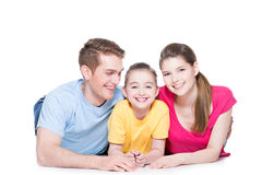 Smiling family with child sitting in colorful shirt. Stock Photo