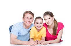 Smiling family with child sitting in colorful shirt. Portrait of happy smiling family with child sitting in colorful shirt lying on the floor at studio stock photos