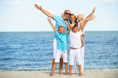 Smiling family with children having fun on the beach. Portrait of smiling family with children having fun on the sunny beach with raised hands stock photo